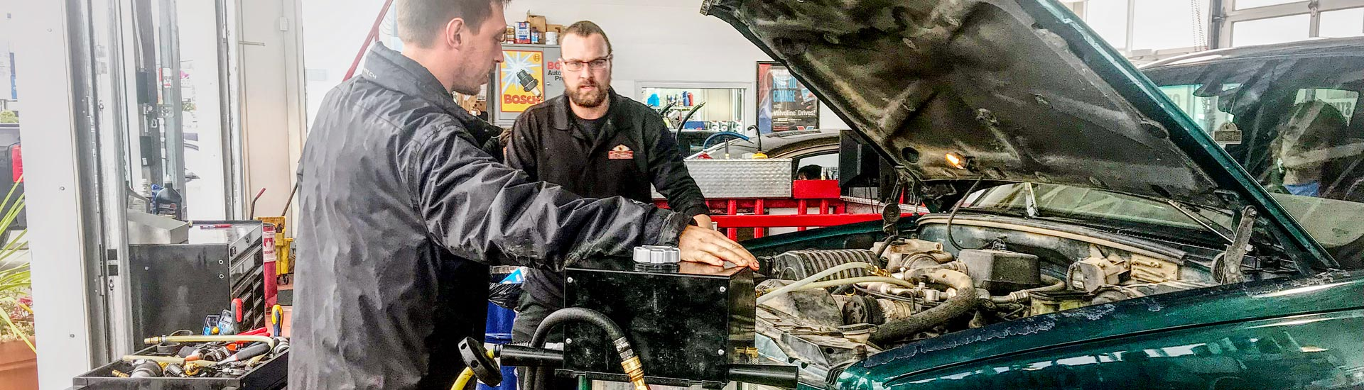 Mechanic fixing green car